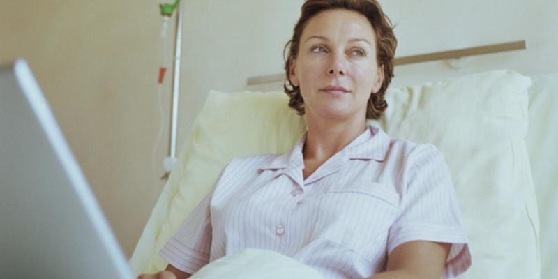 Kvinne i sykehusseng med laptop forbereder seg på ubehag i medisinsk behandling
